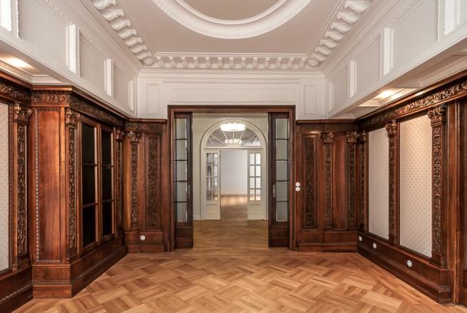 Salon mit oppulenter Holztäfelung, großzügigen Schiebetüren und Stuck an Wand und Decke