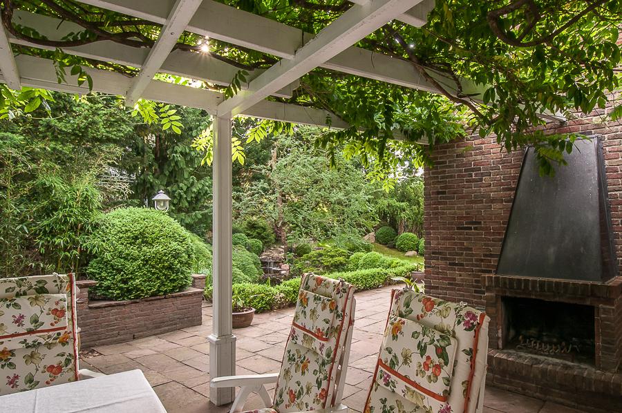 Blick von der Pergola mit Außenkamin auf den Garten