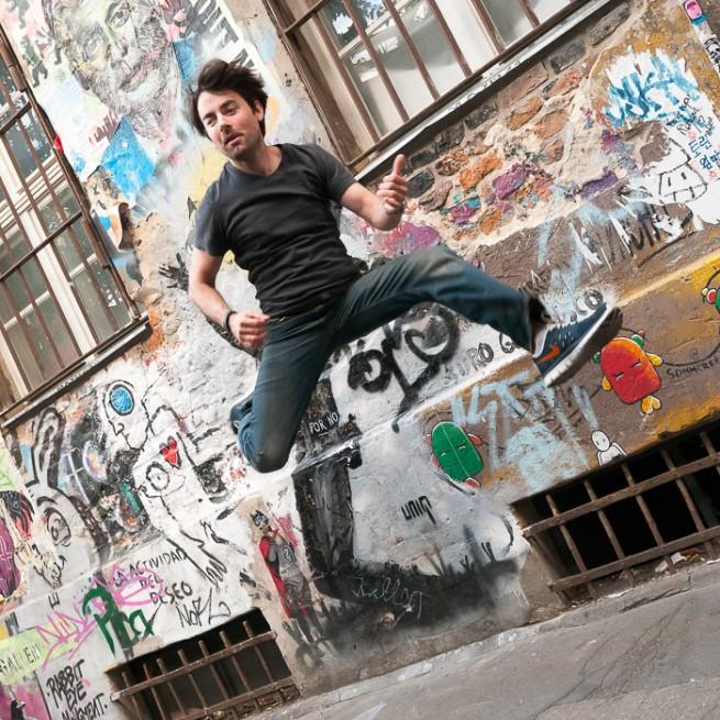 """Patrick Hall bei einem seiner Sprung-Bilder vor einer """"kreativen Collage"""" in Nähe der Hackeschen Höfe."""