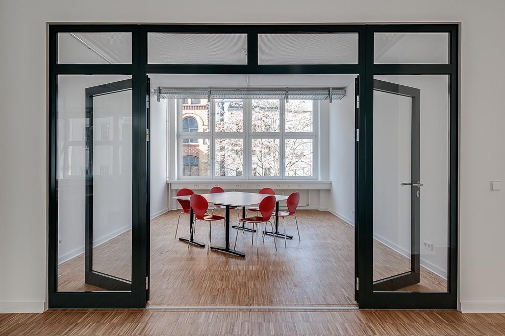 Im Besprechungsraum mit großzügiger Glasfront gegenüber dem Eingangsbereich zitieren acht einfache Möbelstücke die Konferenzsituation.