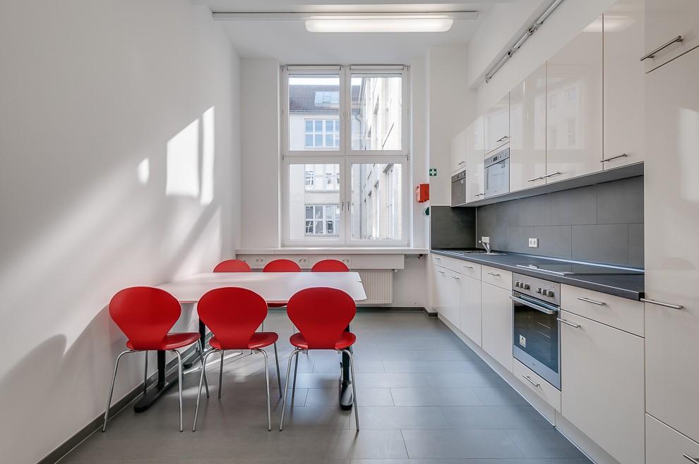 Sechs Stapelstühle und zwei Tische simulieren den Frühstückstisch in der Büroküche.
