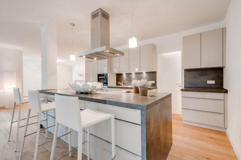 Offene Küche mit Kochinsel und Tresen, im Hintergrund Zugang zur Speisekammer